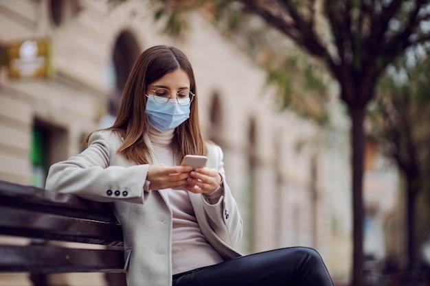 Jeune brune avec un masque facial sur le visage assis sur le banc à l'extérieur et à l'aide d'un téléphone intelligent pour envoyer des sms. la génération y pendant le virus corona.