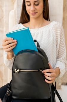 Jeune brune mettant un livre dans un sac à dos