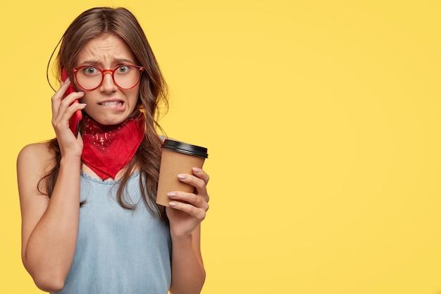 Jeune brune nerveuse avec des lunettes posant contre le mur jaune
