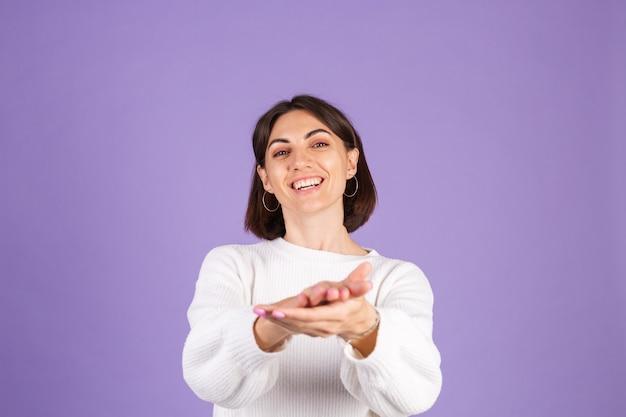 Jeune brune en pull décontracté blanc isolé sur mur violet