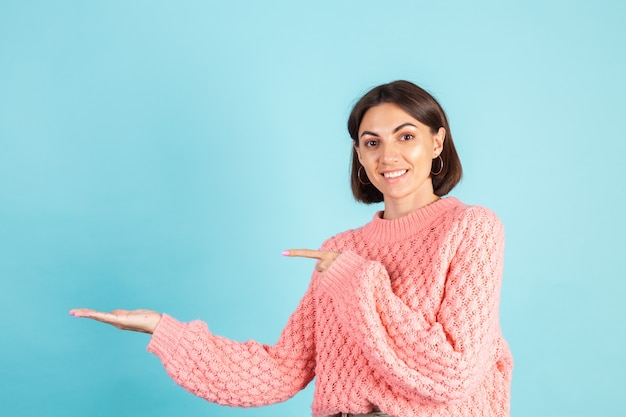 Jeune brune en pull rose isolé sur mur bleu