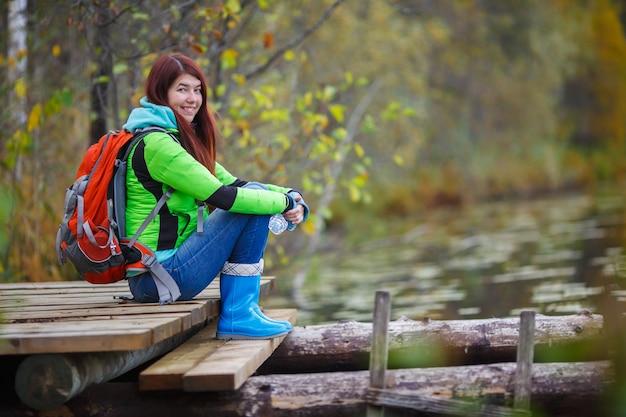 Jeune brune avec sac à dos assis sur le pont de l'étang dans les bois