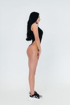 Jeune brune sexy dans un body noir sur fond blanc. la silhouette athlétique parfaite.