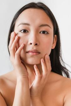 Jeune brunette asiatique touchant le visage avec un torse nu