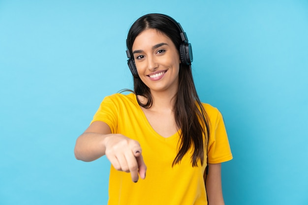 Jeune, brunette, femme, isolé, bleu, mur, écoute, musique