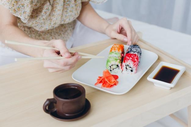 Jeune, brunette, femme, manger, sushi