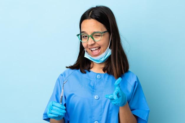 Jeune brunette métisse dentiste femme tenant des outils
