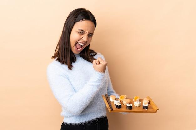 Jeune brunette race mixte woman holding sushi sur isolé pour célébrer une victoire