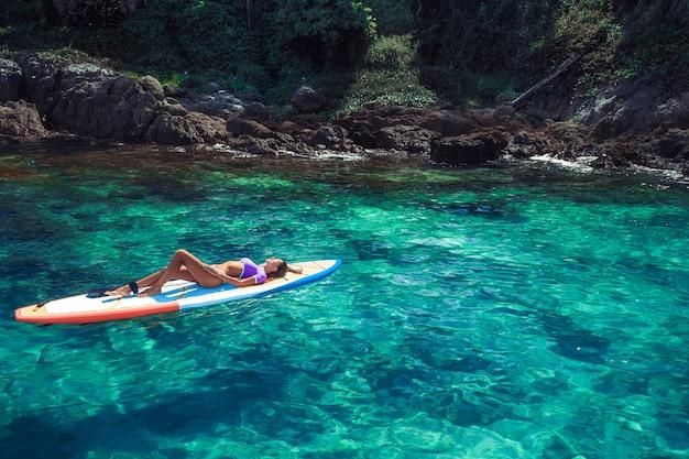 Jeune brunette souriante posant en position couchée dans un bikini rose, sur une planche de surf,