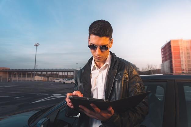 Jeune caucasien à l'aide d'une tablette numérique avec une voiture de sport derrière dans un parking.