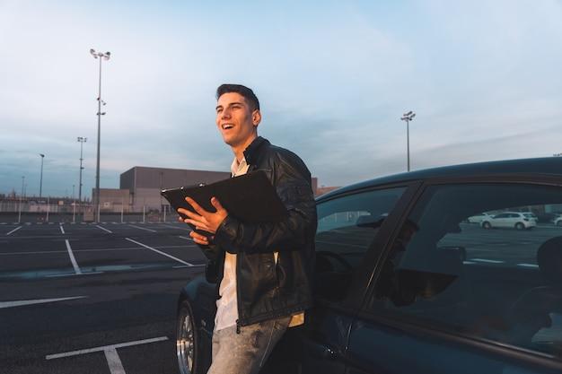 Jeune Caucasien à L'aide D'une Tablette Numérique Avec Une Voiture De Sport Derrière Dans Un Parking. Photo Premium