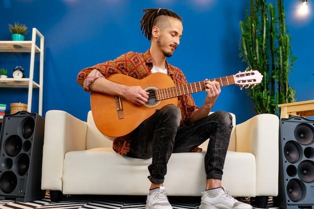 Jeune, caucasien, dreadlocks, séance, sofa, jouer, acoustique, guitare