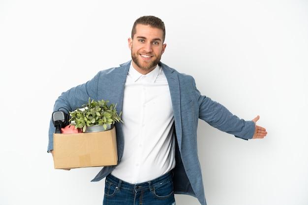 Jeune caucasien faire un mouvement tout en ramassant une boîte pleine de choses isolé sur blanc s'étendant les mains sur le côté pour inviter à venir
