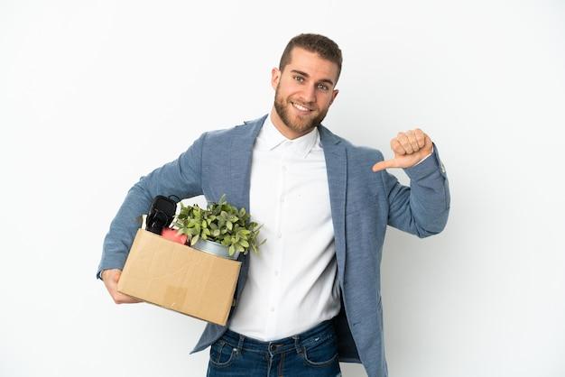 Jeune caucasien faire un mouvement tout en ramassant une boîte pleine de choses isolé sur fond blanc fier et satisfait de soi