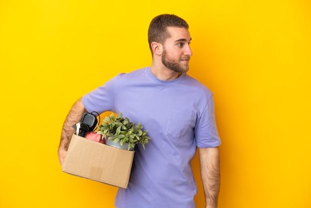 Jeune caucasien faire un mouvement tout en ramassant une boîte pleine de choses isolé sur fond jaune à la recherche sur le côté