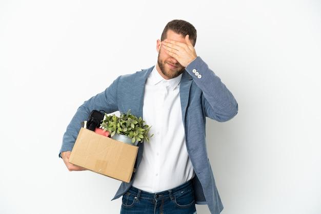 Jeune caucasien faisant un mouvement tout en ramassant une boîte pleine de choses isolées sur un mur blanc couvrant les yeux par les mains. je ne veux pas voir quelque chose