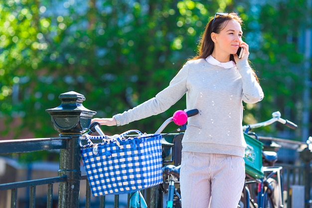 Jeune, caucasien, femme conversation, par, téléphone portable, sur, pont, dans, ville européenne