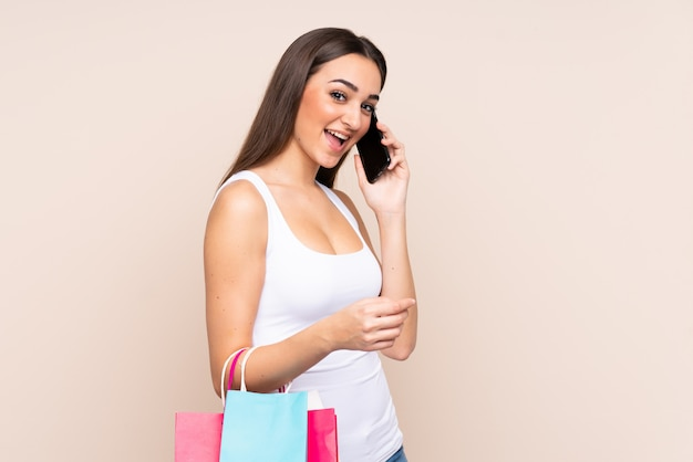Jeune, caucasien, femme, isolé, beige, mur, tenue, achats, sacs, appeler, ami, elle, téléphone portable