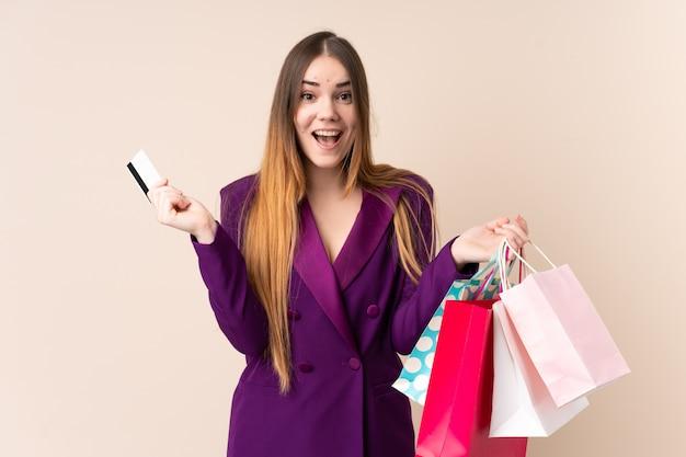 Jeune, caucasien, femme, isolé, beige, mur, tenue, achats, sacs, carte de crédit