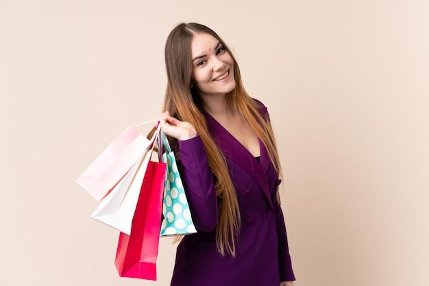 Jeune, caucasien, femme, isolé, beige, mur, tenue, achats, sacs