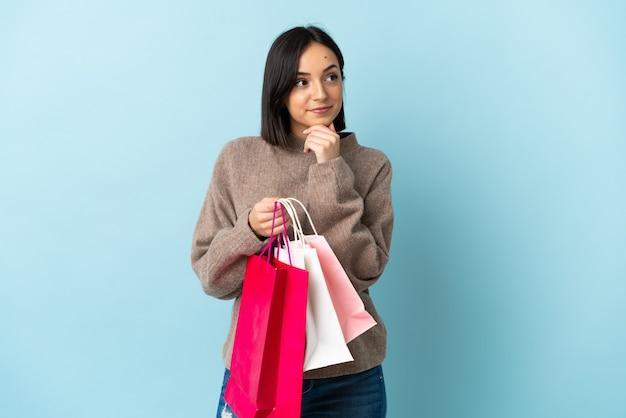 Jeune, caucasien, femme, isolé, sur, bleu, tenue, sacs provisions, et, pensée