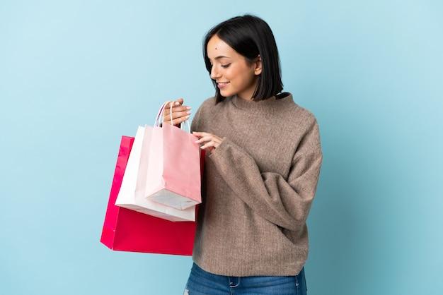 Jeune, caucasien, femme, isolé, sur, bleu, tenue, sacs provisions