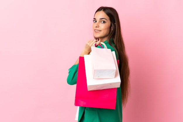 Jeune, caucasien, femme, isolé, sur, rose, tenue, sacs provisions, et, sourire
