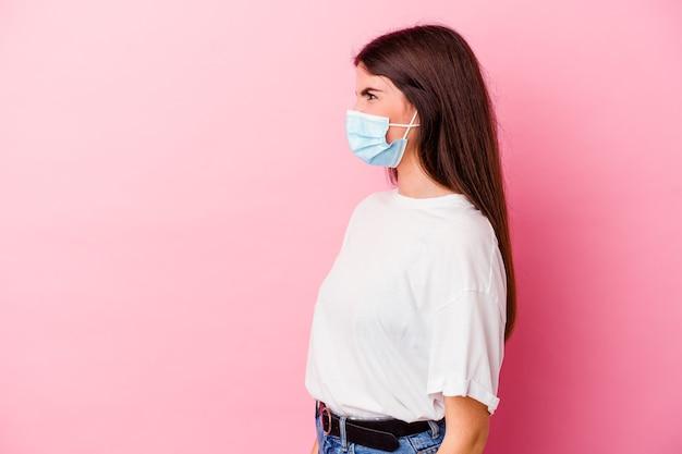 Jeune, caucasien, femme, porter, a, masque, pour, virus, isolé, sur, mur rose