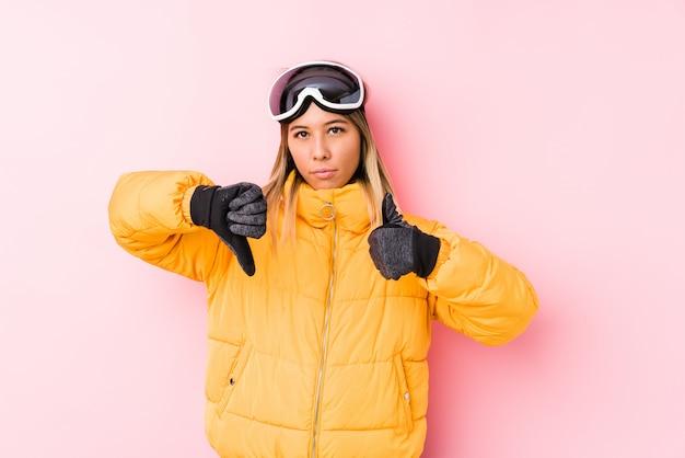 Jeune, caucasien, femme, porter, ski, vêtements, rose, mur, projection, pouces haut, pouces bas, difficile, choisir, concept