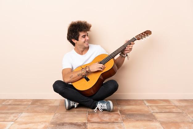 Jeune, caucasien, guitare, séance, plancher, heureux, expression