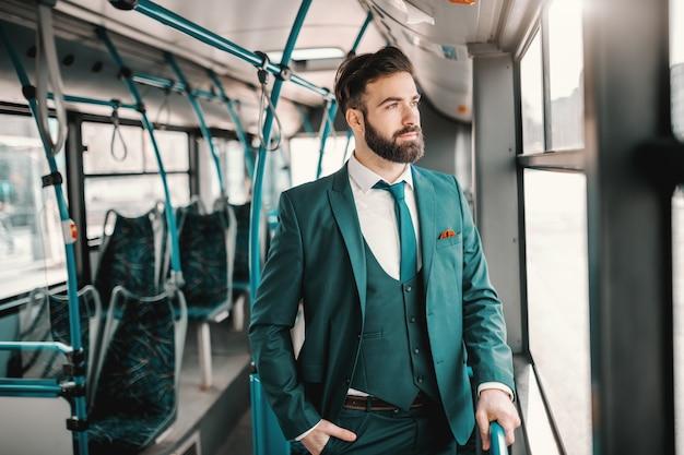 Jeune, caucasien, homme affaires, turquoise, complet, conduite, autobus public, regarder, auge, fenêtre ne quitte pas.