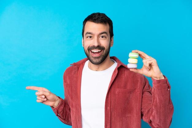 Jeune, caucasien, homme, isolé, bleu, mur, tenue, coloré, français, macarons, pointage, côté