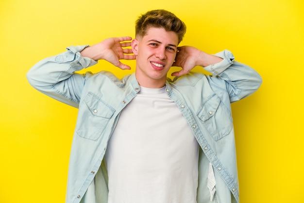 Jeune, caucasien, homme, isolé, sur, mur jaune, étirage, bras, position détendue