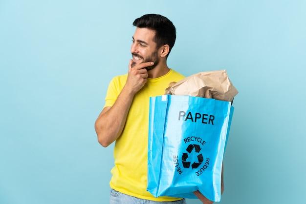 Jeune, caucasien, homme, tenue, recycler, sac, isolé, bleu, mur, pensée, idée, regarder, côté
