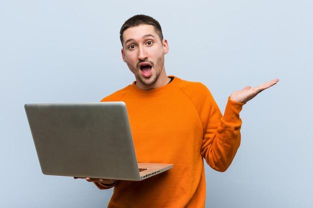 Jeune, caucasien, tenue, ordinateur portable, impressionné, tenue, copie, espace, paume
