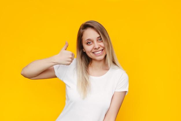Une jeune caucasienne belle femme blonde souriante joyeuse et joyeuse dans un t-shirt blanc montrant le pouce vers le haut comme un geste avec sa main isolée sur un mur jaune de couleur vive