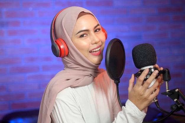 Une jeune chanteuse musulmane souriante portant des écouteurs avec un microphone tout en enregistrant une chanson dans un studio de musique avec des lumières colorées.