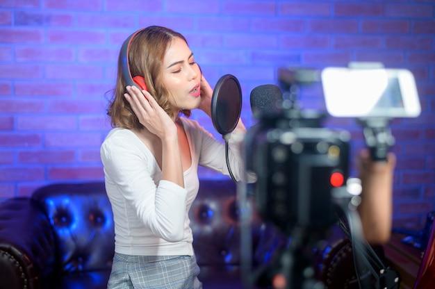 Une jeune chanteuse souriante portant des écouteurs avec un microphone lors de l'enregistrement d'une chanson dans un studio de musique avec des lumières colorées.