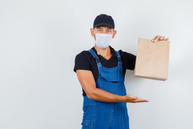 Jeune chargeur montrant un sac en papier brun en uniforme, masque, vue de face.