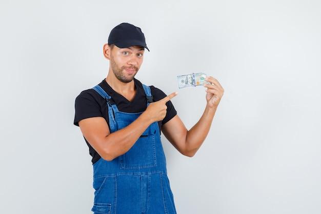 Jeune chargeur pointant sur le billet d'un dollar en uniforme et à la joyeuse vue de face.