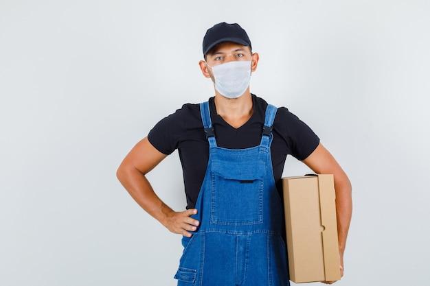 Jeune chargeur tenant une boîte en carton avec la main sur la taille en uniforme, vue de face du masque.