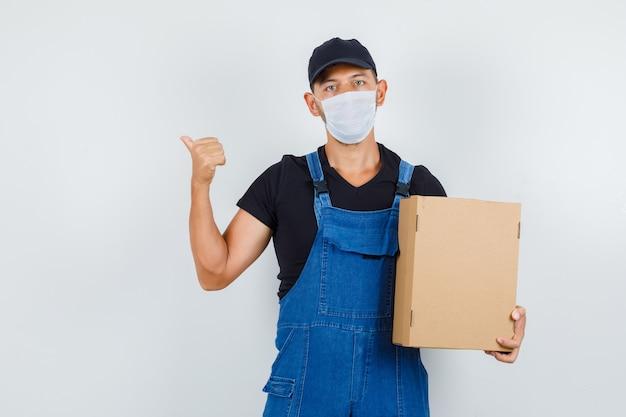 Jeune chargeur tenant une boîte en carton tout en pointant vers l'arrière en uniforme, vue de face du masque.