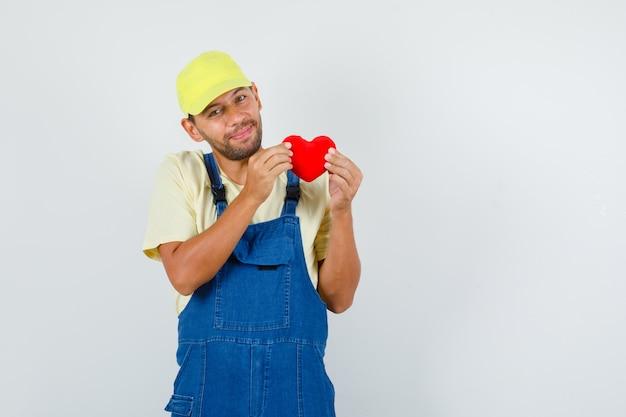 Jeune chargeur tenant coeur rouge en uniforme et à la joyeuse vue de face.