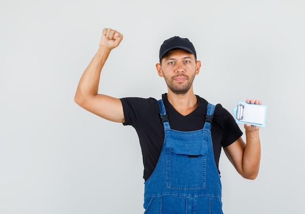 Jeune chargeur tenant un mini presse-papiers avec un geste gagnant en vue de face uniforme.