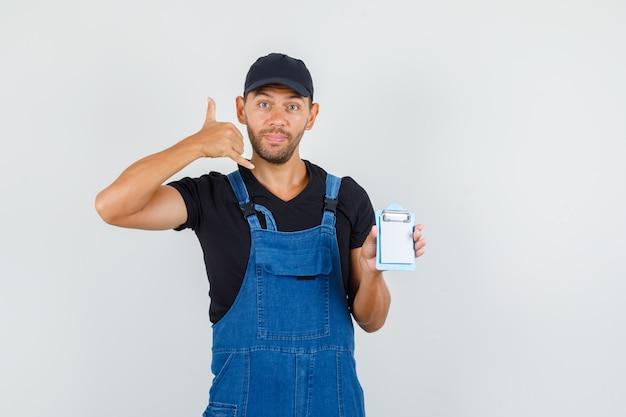 Jeune chargeur tenant un mini presse-papiers avec geste de téléphone en uniforme, vue de face.