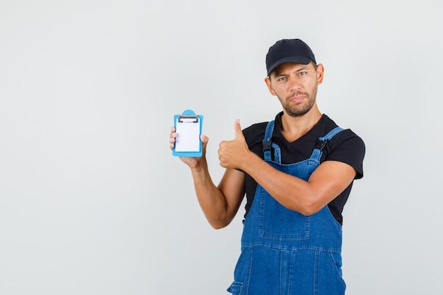 Jeune chargeur tenant un mini presse-papiers avec le pouce vers le haut en uniforme, vue de face.