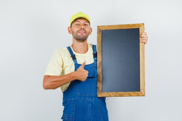 Jeune chargeur tenant tableau noir avec le pouce vers le haut en uniforme et à la bonne humeur. vue de face.