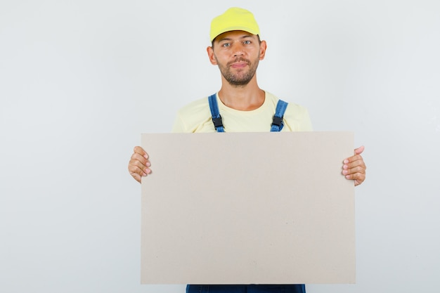 Jeune chargeur tenant une toile vierge et souriant en vue de face uniforme.