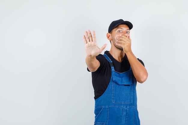 Jeune chargeur en uniforme ne montrant aucun geste avec la main sur la bouche et à la peur, vue de face.