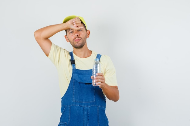 Jeune chargeur en uniforme se sentant chaud avec une bouteille d'eau, vue de face.